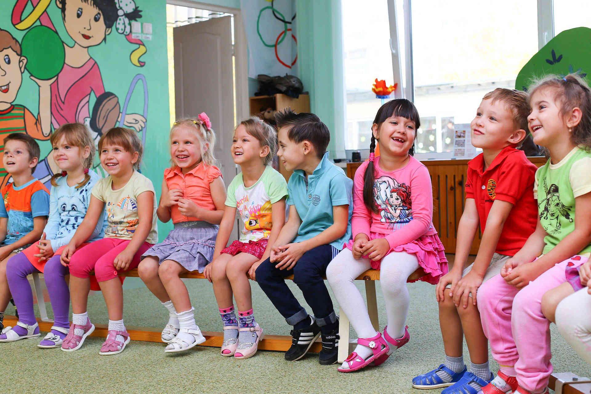 Deca sede na klupi u jednom redu